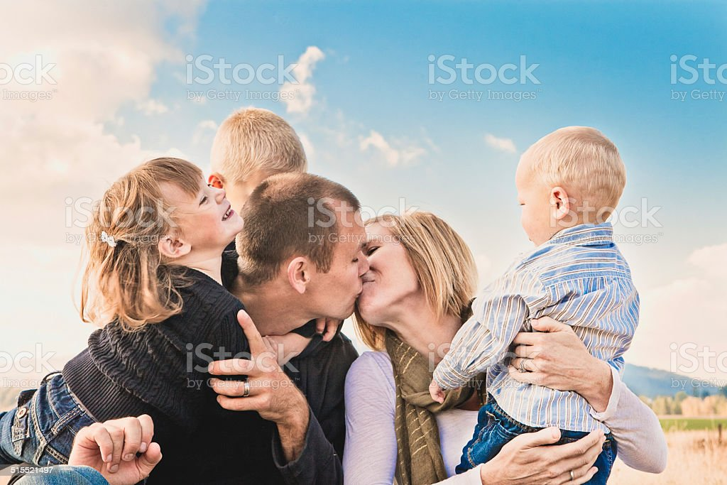 Happy Traditional Family - Loving Parents And Children Together Outdoors stock photo
