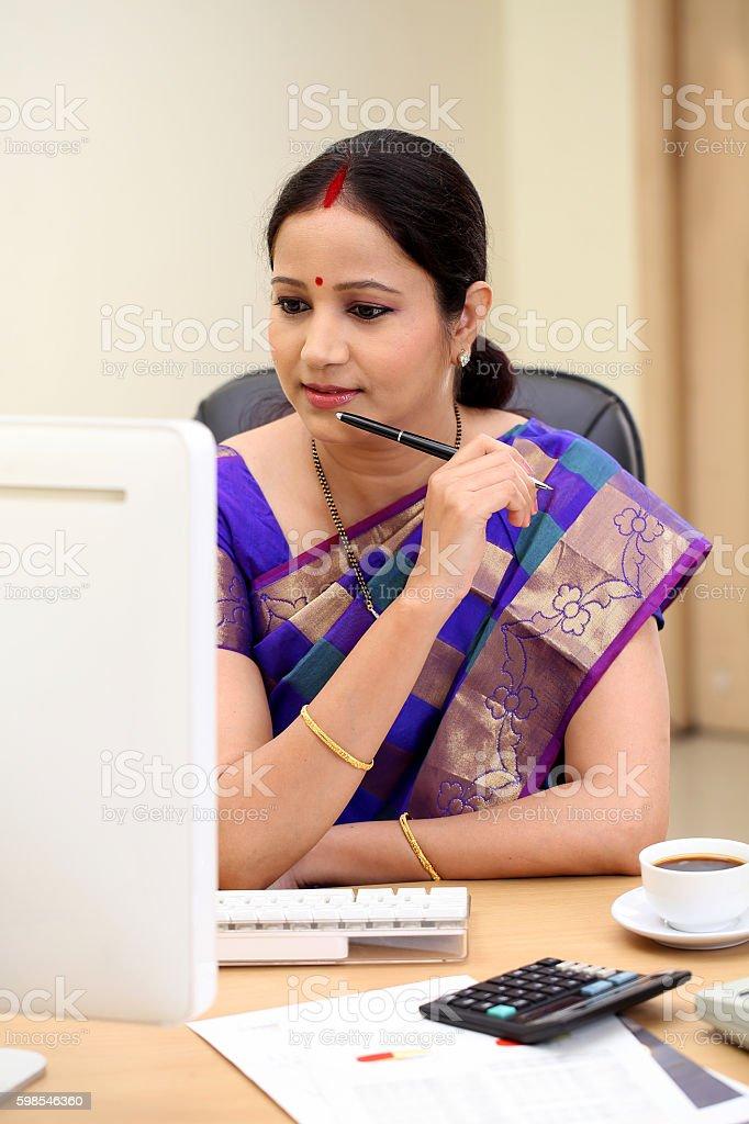 Happy traditional Indian business woman at office desk photo libre de droits