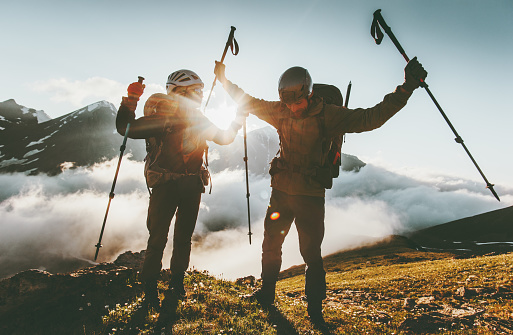 Happy travel couple man and woman on mountain summit love and adventure hiking Lifestyle wanderlust concept sunset light