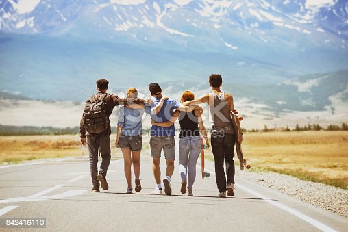 Group of five happy friends going ahead on straight road. Space for text