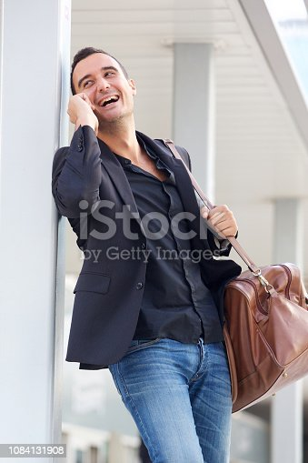 istock happy travel man with bag talking on smart phone 1084131908