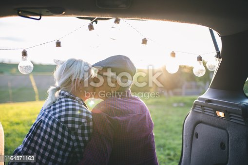 Happy traveler couple sitting in car open trunk and communicate at sunrise