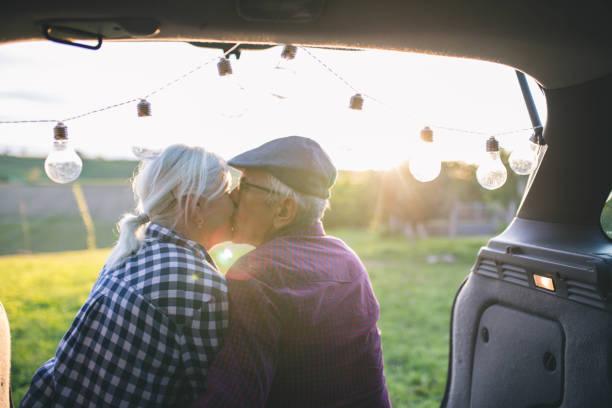 glückliches reisendes paar sitzt im auto offenen kofferraum und kommunizieren bei sonnenaufgang - romantisches picknick stock-fotos und bilder