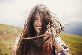 happy traveler hipster girl with windy hair and smiling, standing on top of sunny mountains. space for text. stylish woman waving hair. atmospheric moment. travel and wanderlust