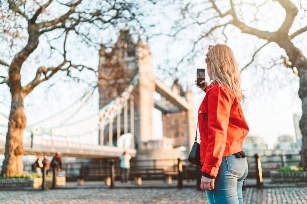 Happy traveler sightseeing London, taking a photo of Tower bridge stock photo