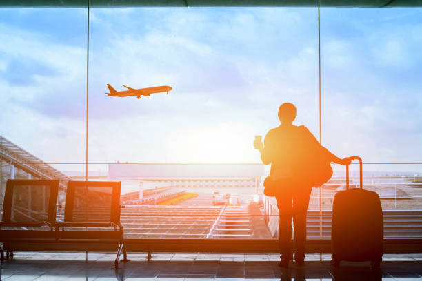 happy traveler waiting for the flight in airport - international moving stock photos and pictures