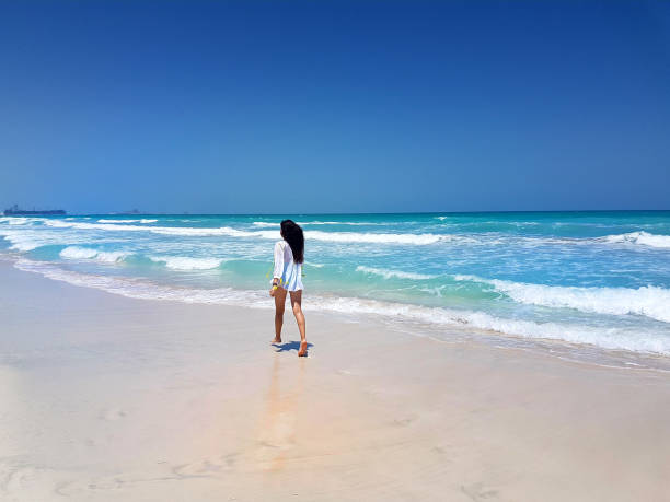 Femme heureuse de voyageur marche sur une plage tropicale. - Photo