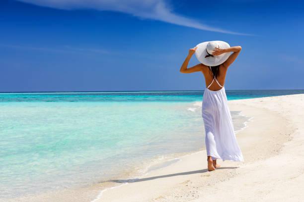 mutlu traveler kadın tropikal bir kumsalda yürür - beyaz elbise stok fotoğraflar ve resimler