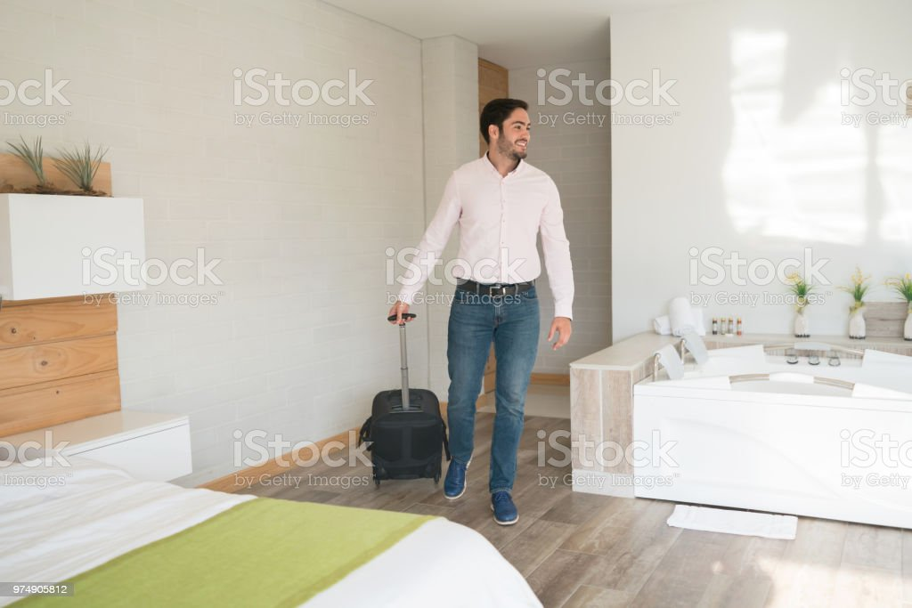 Happy traveling man entering his room at the hotel carrying his...