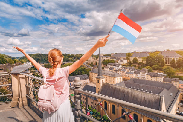 A happy traveller girl holds the flag of Luxembourg and admires the Grund area from the observation deck. Tourism, recreation and life in the country. stock photo