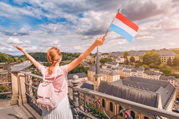 Ein glückliches Reisendes Mädchen hält die Flagge von Luxemburg und bewundert das Grund-Gebiet von der Aussichtsplattform. Tourismus, Erholung und Leben auf dem Land. – Foto