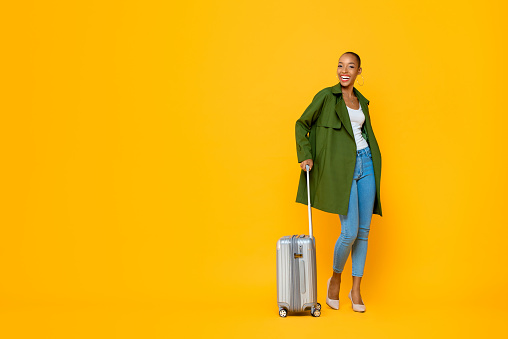 Full length portrait of travelling happy young African American tourist woman standing while holding luggage in isolated studio yellow background