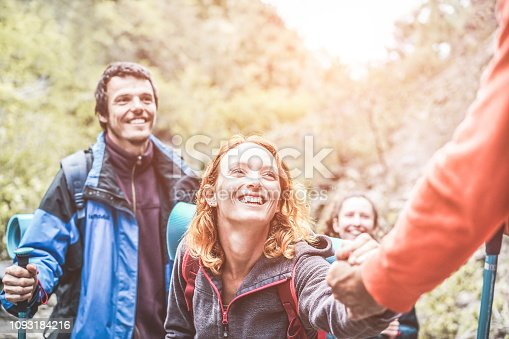 istock Happy trekkers helping each others hiking on mountaing path - Real people faces having fun on trekking day - Survival, helping, travel, team and adventure concept - Focus on girl face 1093184216