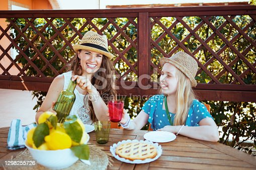 istock happy trendy family sitting at table having lunch 1298255726
