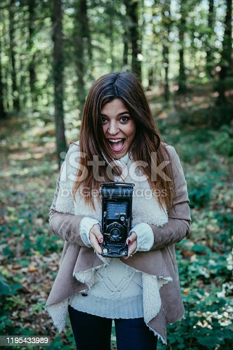 Young beautiful girl enjoying a walk in the woods and taking pictures with an old camera.