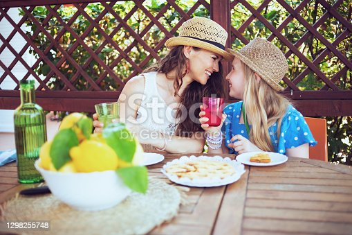 istock happy trendy mother and daughter sitting at table having lunch 1298255748
