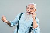 Happy trendy senior man having fun posing in front camera - Fashion beard mature male enjoying retired time - Elderly people lifestyle and hipster culture concept