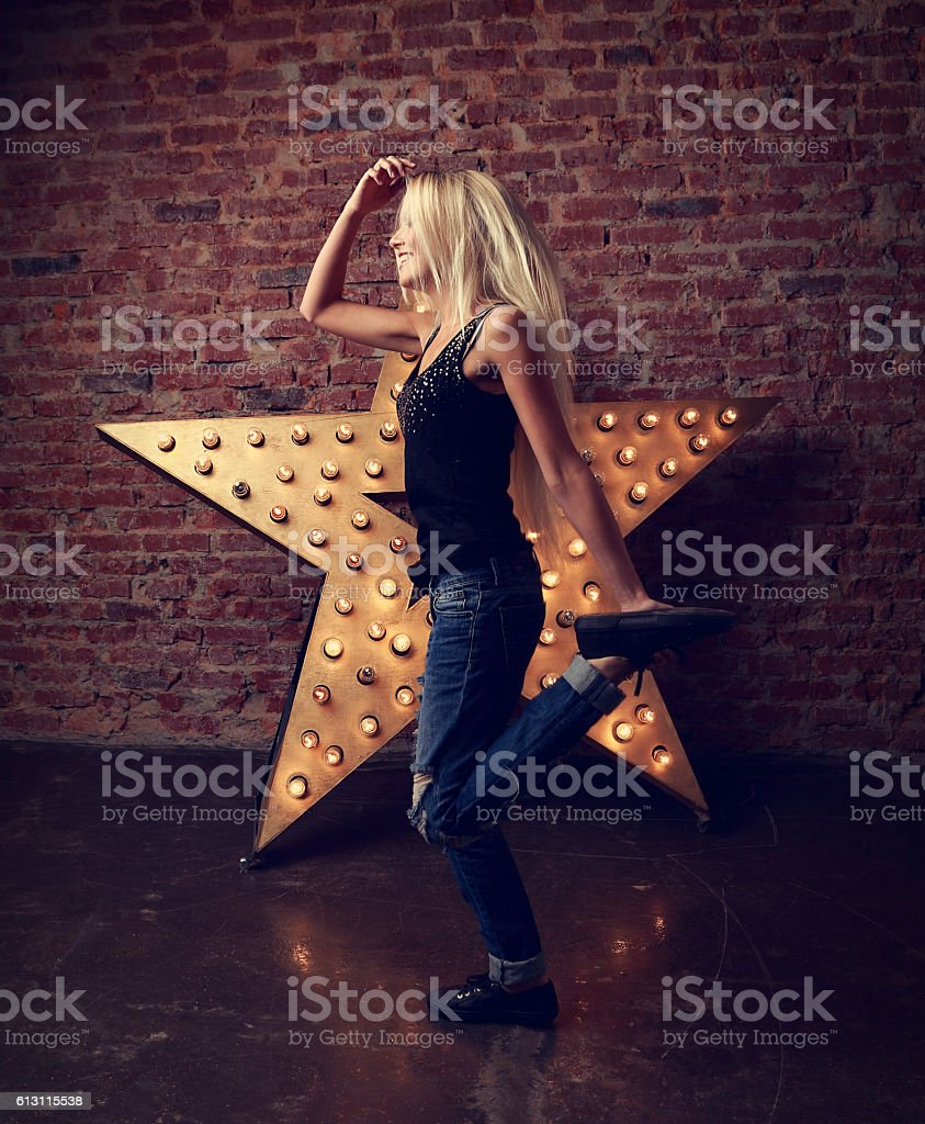Happy trendy teen girl dancing and jumping on yellow star stock photo
