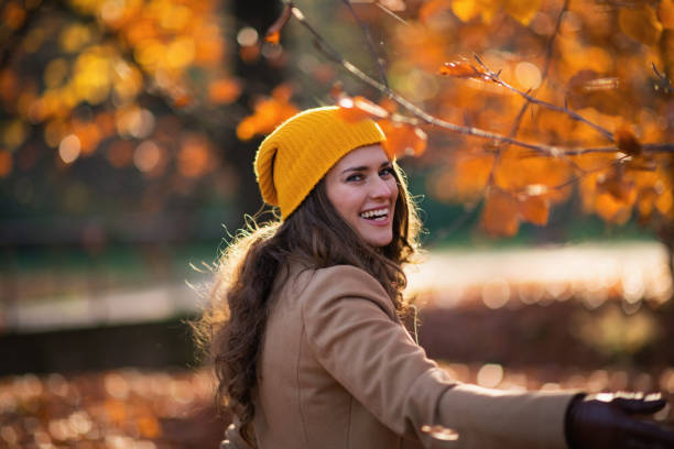 happy trendy woman in brown coat and hat having fun time stock photo