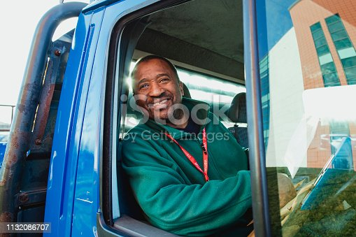 Senior truck driver is smiling while pulling out of a parking lot in his work truck.