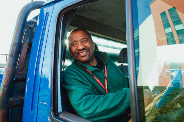 Happy Truck Driver Senior truck driver is smiling while pulling out of a parking lot in his work truck. driver occupation stock pictures, royalty-free photos & images
