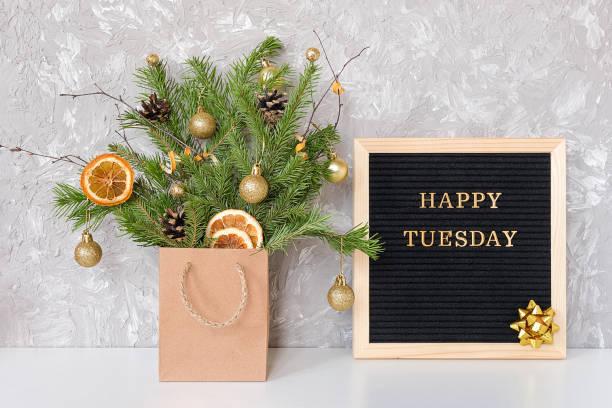 happy tuesday text auf schwarzem brief tafel und festlichen strauß von tannenzweigen mit weihnachtsdekor in handwerk paket auf dem tisch. vorlage für postkarte, grußkarte konzept hallo winter dienstag - zitate weihnachten stock-fotos und bilder