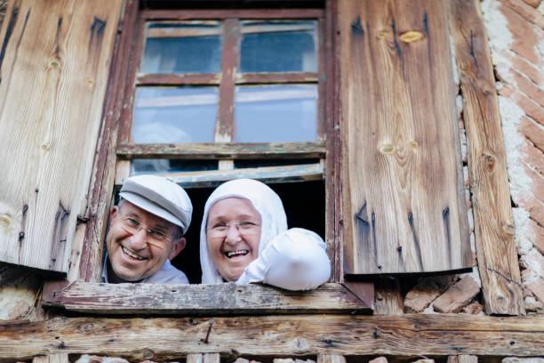 gelukkig turkse echtpaar op zoek door raam - turkse etniciteit stockfoto's en -beelden