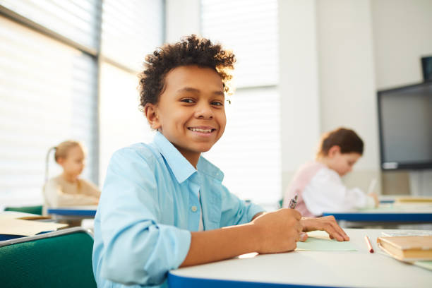 Happy Twelve-Year-Old Student Smiling Horizontal low angle medium close up portrait of happy mixed-race boy with kinky hair sitting at school desk looking at camera smiling, copy space middle school teacher stock pictures, royalty-free photos & images