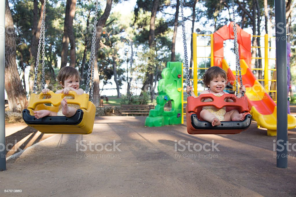 happy twin baby sisters enjoying in swing in park stock photo