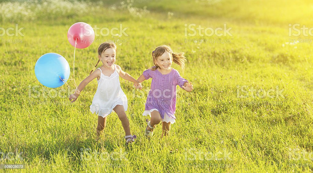 happy twin sisters running around laughing and playing with balloons stock photo