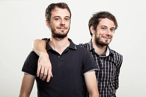 Happy Twins Two Happy Twins Hugging brother stock pictures, royalty-free photos & images