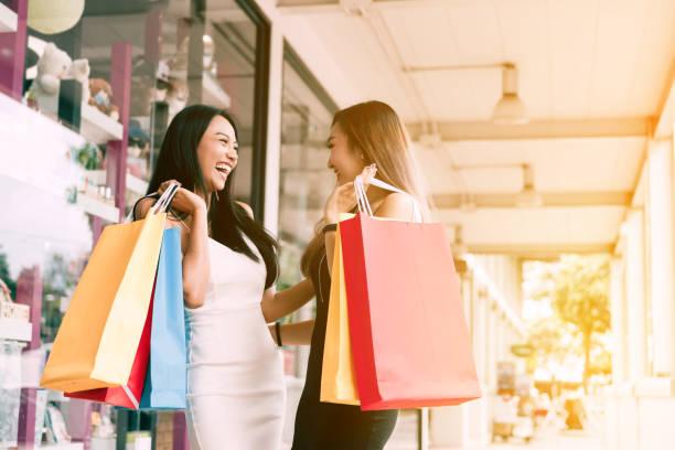 glücklich zwei asiatische frau genießen tun zusammen in der mitte der mall einkaufen. - heute ist freitag stock-fotos und bilder