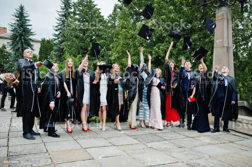 Happy university graduates throwing their graduation caps into the air. stock photo