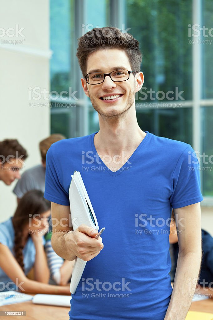 Happy university student Young adult man holding workbook and smiling at the camera with group of high school students studying together in the background.  20-24 Years Stock Photo