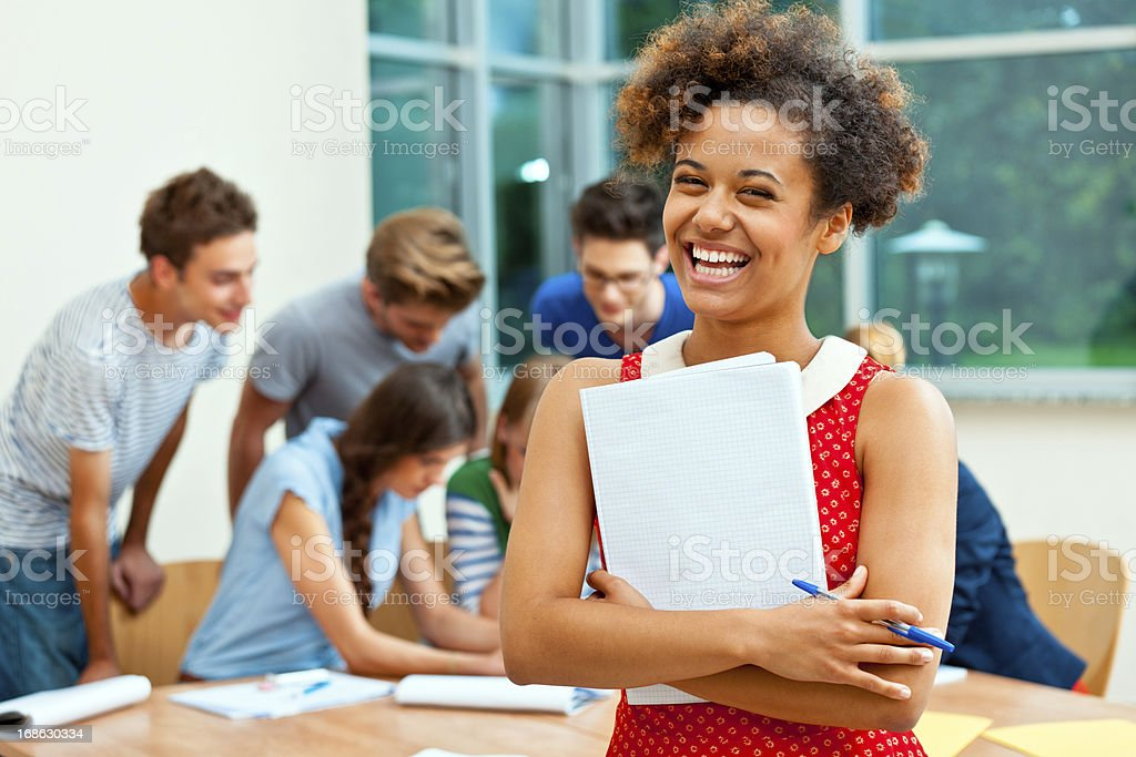 Happy university student Young adult woman holding workbook and smiling at the camera with group of high school students studying together in the background.  20-24 Years Stock Photo