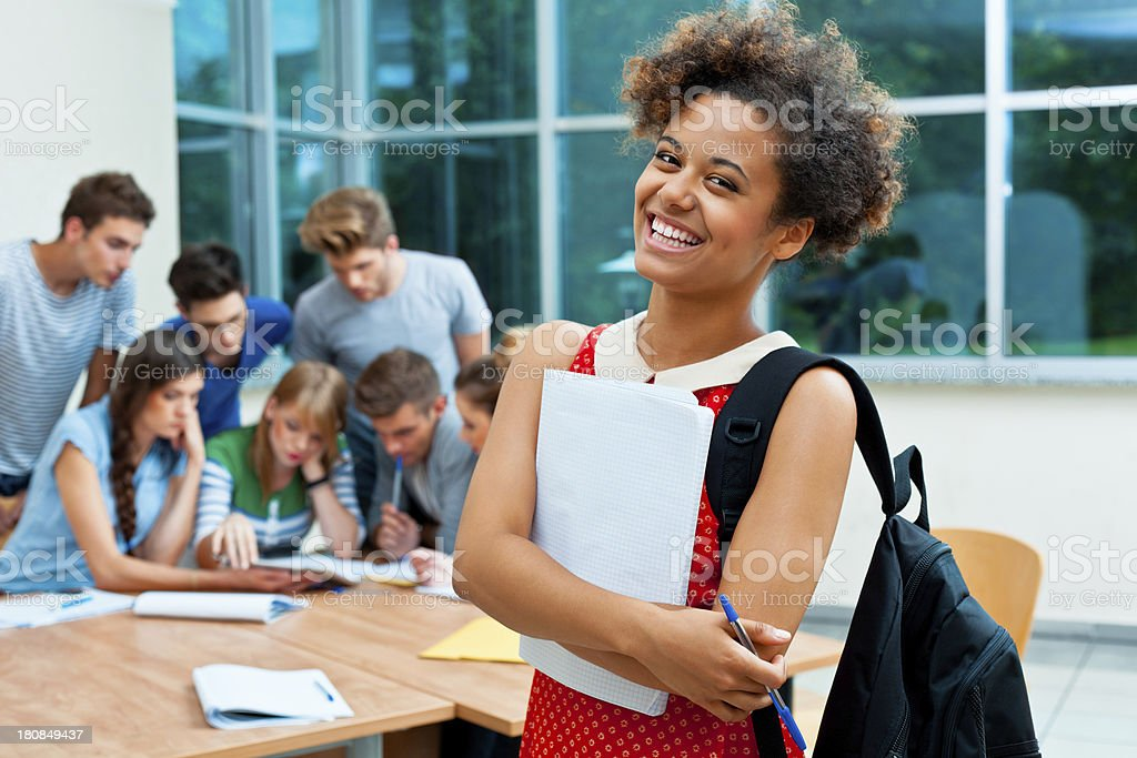 Happy university student Female student holding workbook and smiling at the camera with group of college students working together in the background.  20-24 Years Stock Photo