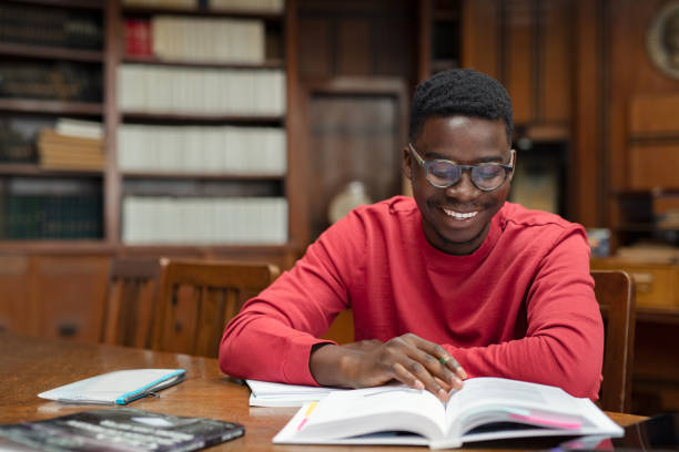 Happy university student reading in library stock photo