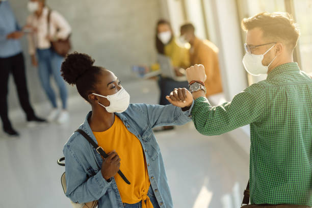Happy university students greeting with elbow while wearing protective face masks. stock photo