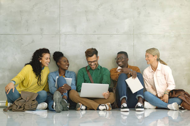 Happy university students using laptop while sitting in a hallway. stock photo