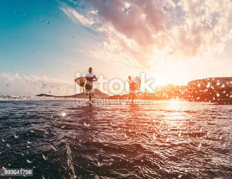 Happy urfers running with surf boards on the beach - Sporty people having fun in sunny day - Extreme sport, travel and vacation concept - Focus on bodies silhouettes - Water on camera lens