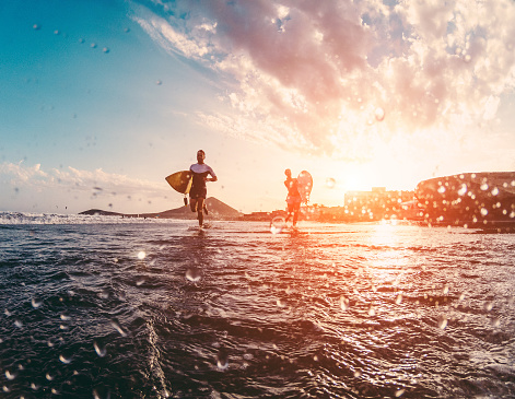 istock Happy urfers running with surf boards on the beach - Sporty people having fun in sunny day - Extreme sport, travel and vacation concept - Focus on bodies silhouettes - Water on camera lens 893041756
