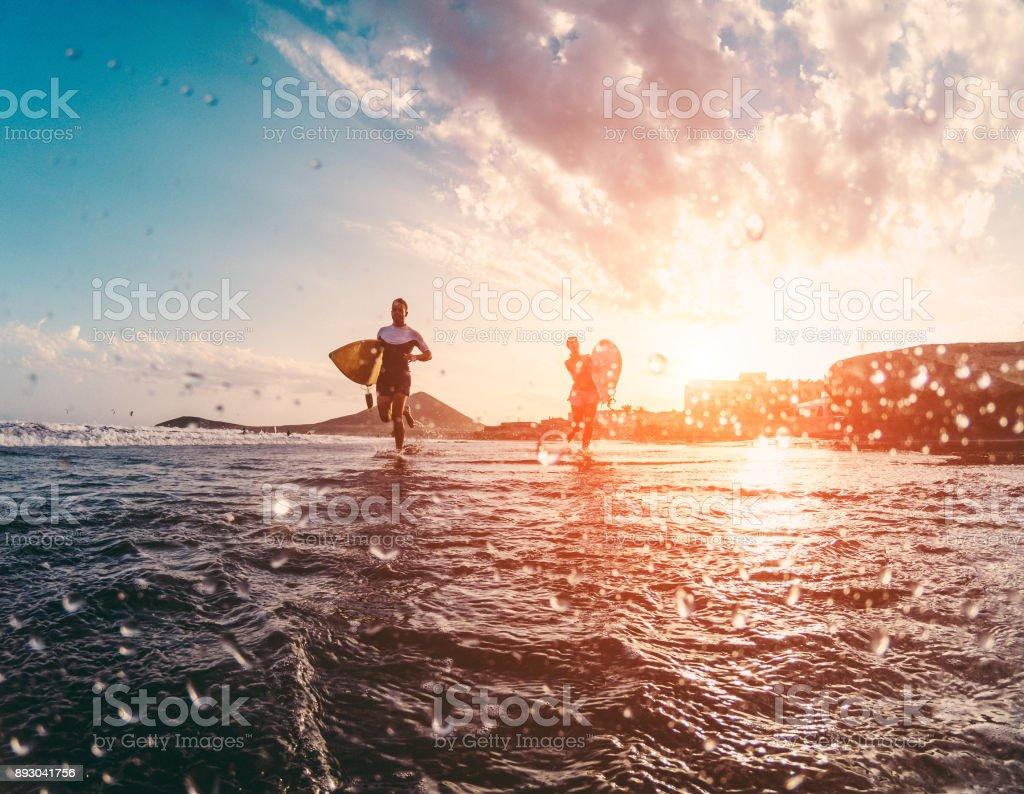 Glücklich Urfers laufen mit Surfbrettern auf dem Strand - sportliche Leute, die Spaß an sonnigen Tagen - Extreme Sport, Reisen und Urlaub Konzept - Fokus auf Körper Silhouetten - Wasser vor der Kamera Objektiv – Foto