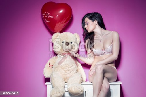 Pretty blond women hold an Valentin heart red balloon