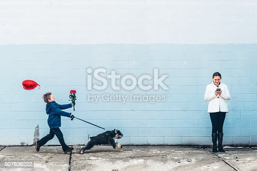 We all need a little help finding love, no matter what tools we use. Little boy with flowers and heart shaped balloon getting pulled by his dog and girl standing using her smartphone looking for something.
