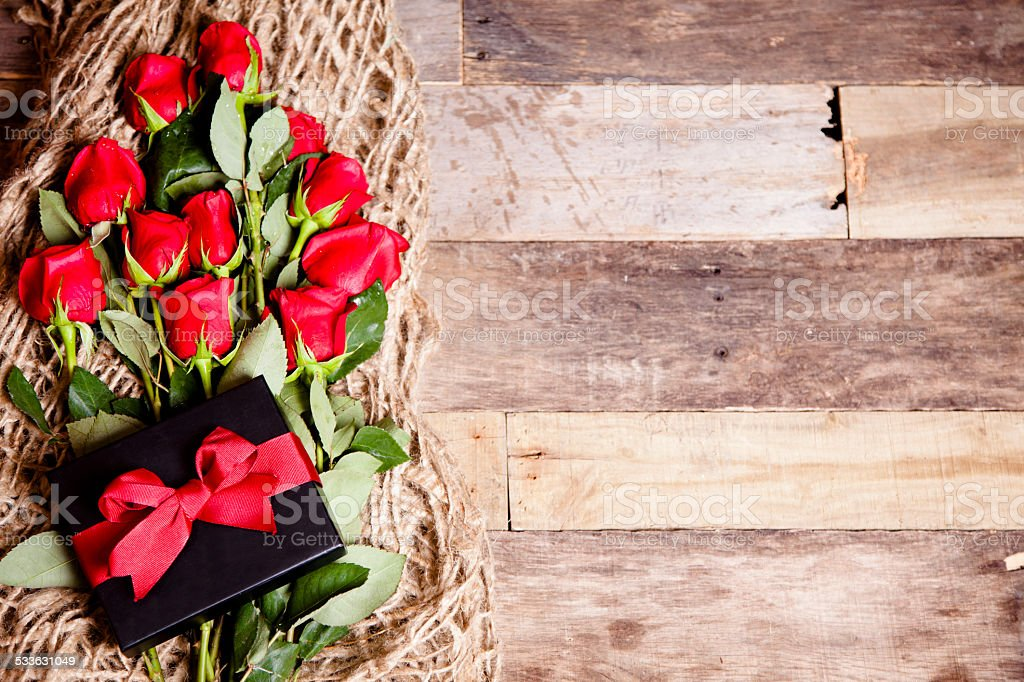 Happy Valentine's Day. Red roses bouquet, gift box. Wooden table. stock photo