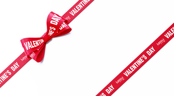 Happy Valentine's Day written red ribbon with tied bow over white background. Horizontal composition with clipping path and copy space. Valentine's Day concept.