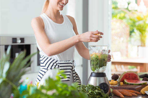 Happy vegan woman mixing vegetables Happy vegan woman mixing healthy smoothie with vegetables blender stock pictures, royalty-free photos & images