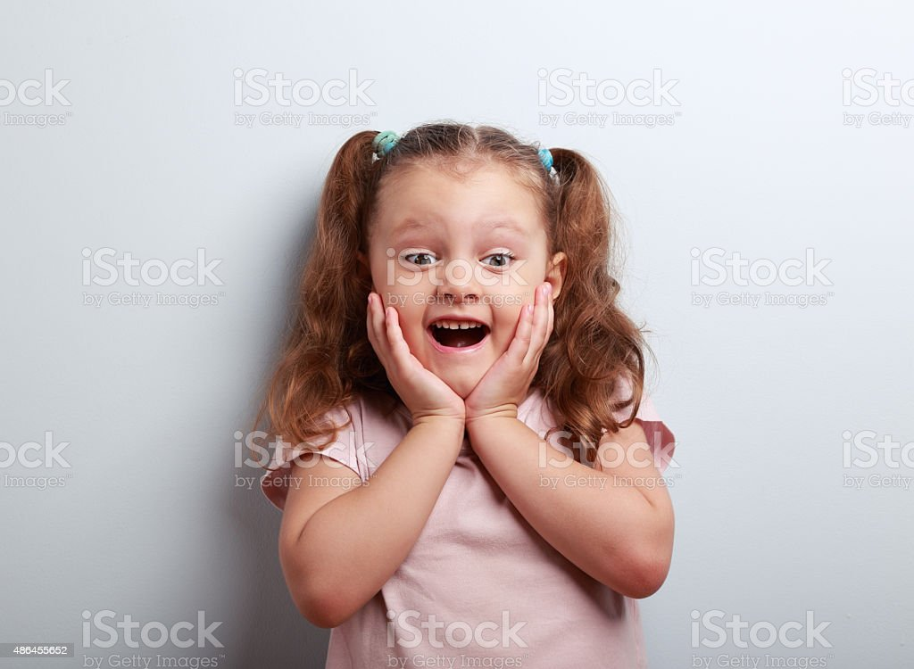Happy very excited kid girl with open mouth looking. Closeup stock photo