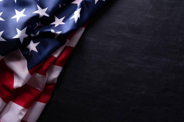 happy veterans day. american flags veterans against a blackboard background. - veterans day стоковые фото и изображения