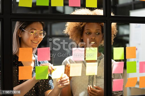 1144569896 istock photo Happy vietnamese employee working with concentrated african american trainee. 1193713016